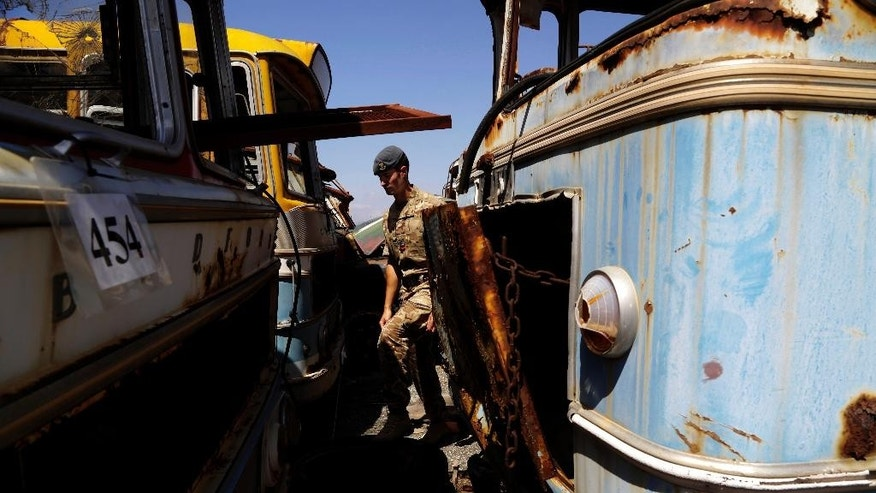 A British soldier walks past abandoned buses at the British military base in Episkopi near the southern coastal city of Limassol in the Mediterranean island of Cyprus, on Wednesday, May 25, 2016.  The cars were abandoned by Turkish Cypriot owners inside a British military base amid the confusion of a war 42 years ago that cleaved Cyprus along ethnic lines.  Now base authorities are hoping to reawaken the interest of owners to reclaim these vehicles before their disposal starts next year. (AP Photo/Petros Karadjias)