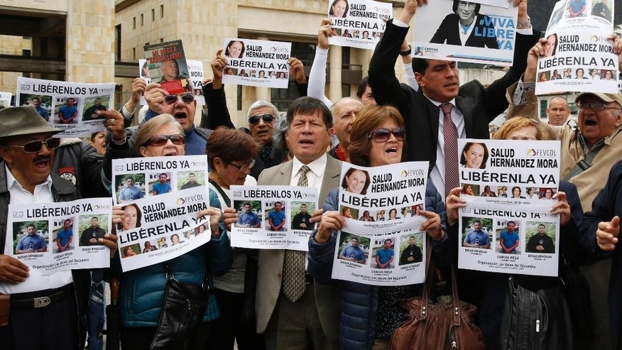 Demonstrators hold signs to demand the release of three journalists who are believe to have been taken hostage, during a sit-in in Bogota, Colombia, Wednesday, May 25, 2016. Salud Hernandez-Mora, correspondent in Colombia for Spain's El Mundo and columnist for the Bogota daily El Tiempo, as well as Diego D'Pablos and Carlos Melo, journalists at the local TV network RCN, are reported missing on the northeastern Colombia's border with Venezuela, a mountainous area dominated by leftist rebels and drug-traffickers. (AP Photo/Fernando Vergara)