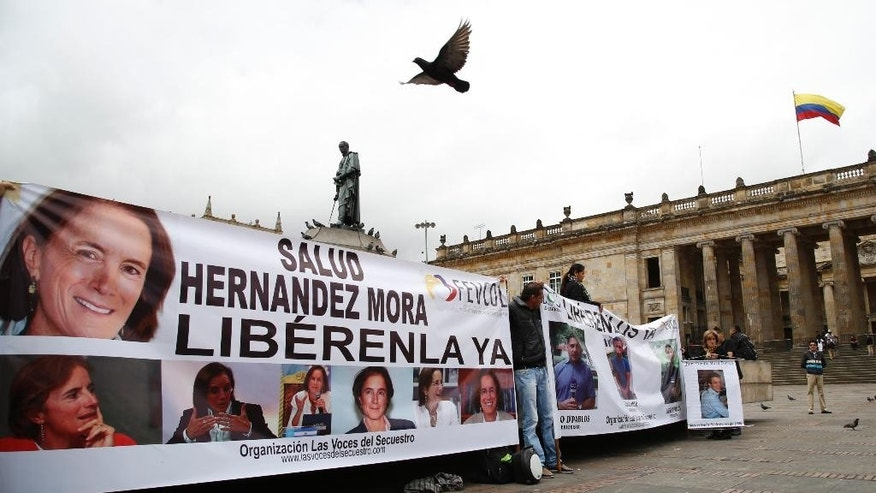 Demonstrators hold banners asking for the release of three journalists who are believe to have been taken hostage, during a sit-in in Bogota, Colombia, Wednesday, May 25, 2016. Salud Hernandez-Mora, correspondent in Colombia for Spain's El Mundo and columnist for the Bogota daily El Tiempo, as well as Diego D'Pablos and Carlos Melo, journalists at the local TV network RCN, are reported missing on the northeastern Colombia's border with Venezuela, a mountainous area dominated by leftist rebels and drug-traffickers. (AP Photo/Fernando Vergara)