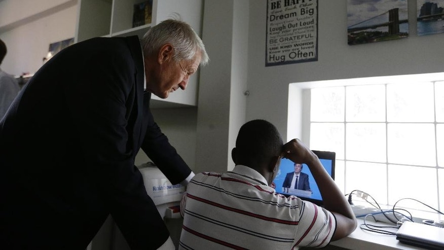 "Council of Europe Secretary General Thorbjorn Jagland, left, stands next to a migrant boy as they watch a French channel on a laptop at a facility housing unaccompanied children in Athens, Thursday, May 26, 2016. Jagland, one of Europe's top human rights officials, says it is ""unacceptable"" that any refugee and migrant children who arrive on the continent unaccompanied by their parents are held in detention centers, and called on European countries to ensure such children can be housed in special facilities and quickly reunited with their families. (AP Photo/Thanassis Stavrakis)"
