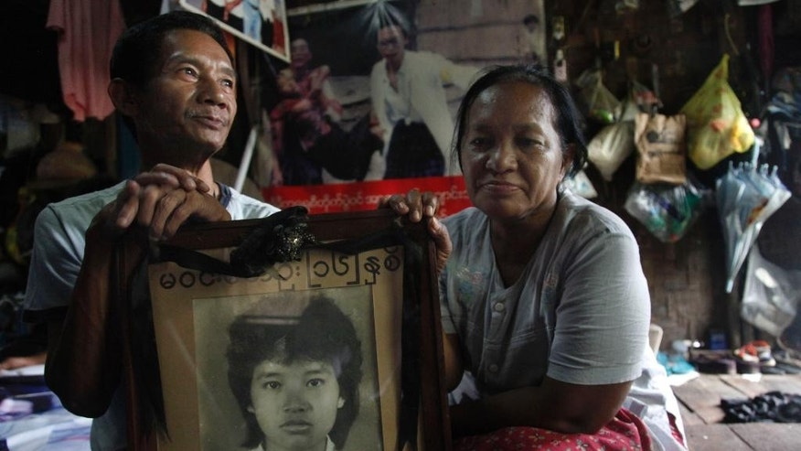 FILE- In this Aug. 1, 2013 file photo, Win Kyu, left, and his wife Khin Htay Win hold a portrait of their 16-year-old daughter Win Maw Oo, who was killed during pro-democracy protests brutally crushed by Myanmar's military 25 years ago, in their house in Yangon, Myanmar. The parents of a Oo after all these years finally laid her soul to rest this week. The funeral ceremony, 28 years late, was delayed because the 16-year-old girl's dying wish was not to have the rites performed until Myanmar _then called Burma _ had achieved democracy. (AP Photo/Khin Maung Win, File)