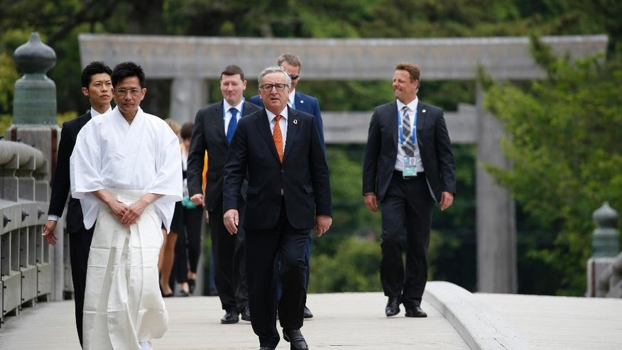 European Commission President Jean-Claude Juncker, center, walks over Ujibashi bridge as he visits the Ise Jingu shrine in Ise, Mie prefecture, Japan, Thursday, May 26, 2016, ahead of the first session of the G-7 summit meetings. The leaders of the G-7 nations have arrived for a visit at Ise Jingu, the most hallowed site for Japan's indigenous Shinto religion. (Toru Hanai/Pool Photo via AP)