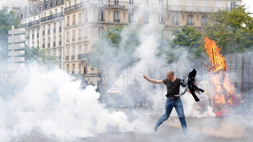 A protestor holding a white rose runs from tear gas fired by police during a demonstration held as part of nationwide labor actions in Paris, Thursday, May 26, 2016. Paris police have detained people and scuffled with masked protesters as several thousand marched through the French capital to demand that the government scrap a labor bill. (AP Photo/Francois Mori)
