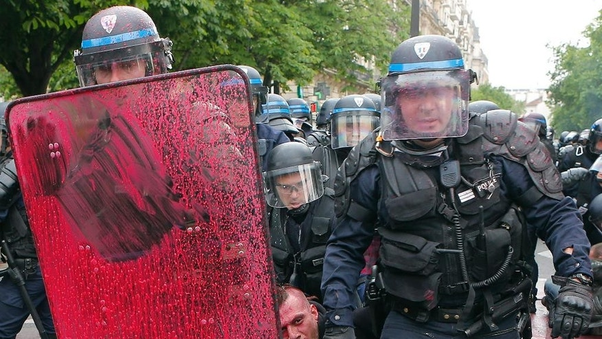 Riot police officers detain a protestor during a demonstration held as part of nationwide labor actions in Paris, France, Thursday, May 26, 2016. French protesters scuffled with police, dock workers set off smoke bombs and union activists disrupted fuel supplies and nuclear plants Thursday in the biggest challenge yet to President Francois Hollande's government as it tries to give employers more flexibility (AP Photo/Francois Mori)