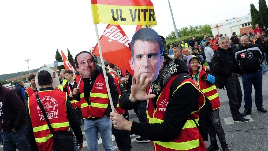 "Union activists wearing masks of French Prime Minister Manuel Valls, right, and French President Francois Hollande, demonstrate while blocking the entrance of the industrial area in Vitrolles near Marseille,  southern France, on a day of nationwide strikes and protests over a labor reform, Thursday, May 26, 2016. French Prime Minister Manuel Valls says he is open to ""improvements and modifications"" in a labor bill that has sparked intensifying strikes and protests, but will not abandon it. (AP Photo/Franck Pennant)"