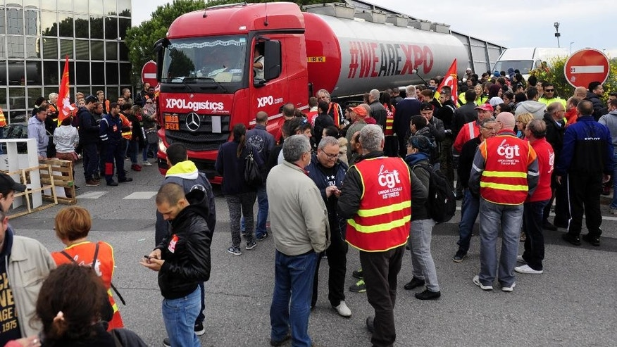 "Union activists block the entrance of the industrial area in Vitrolles near Marseille,  southern France, on a day of nationwide strikes and protests over a labor reform, Thursday, May 26, 2016. French Prime Minister Manuel Valls says he is open to ""improvements and modifications"" in a labor bill that has sparked intensifying strikes and protests, but will not abandon it. (AP Photo/Franck Pennant)"