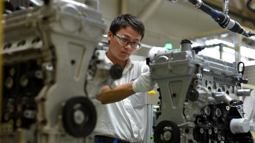 In this Tuesday, Sept. 23, 2014 photo, a worker assembles engine blocks at the General Motors assembly plant in Wuhan in central China's Hubei province. General Motors Co.'s main Chinese joint venture is recalling 2.2 million cars to deal with insufficient corrosion resistance on crankcase valves. The recall was ordered after Shanghai-GM received complaints about engine damage, according to the country's product quality regulator. The automaker is a joint venture between GM and state-owned Shanghai Automotive Industries Corp. (Chinatopix via AP) CHINA OUT