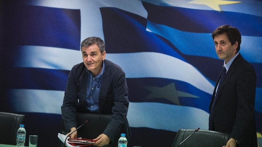 Greek Finance Minister Euclid Tsakalotos, left and deputy Finance Minister Giorgos Houliarakis arrive at a news conference about Greece's bailout program, in Athens ,Thursday, May 26, 2016. Bailout-dependent Greece has agreed to carry out new austerity measures and reforms to secure vital rescue loans from its European creditors. (AP Photo/Petros Giannakouris)