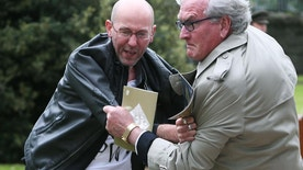 """Canadian Ambassador to Ireland Kevin Vickers, right, wrestles with a protester during a State ceremony to remember the British soldiers who died during the Easter Rising at Grangegorman Military Cemetery, Dublin Thursday May 26, 2016.  Vickers helped subdue a demonstrator who began chanting """"insult"""" at the service commemorating more than 100 British soldiers killed trying to suppress the Easter Rising a century ago.  (Brian Lawless/PA via AP) UNITED KINGDOM OUT"""