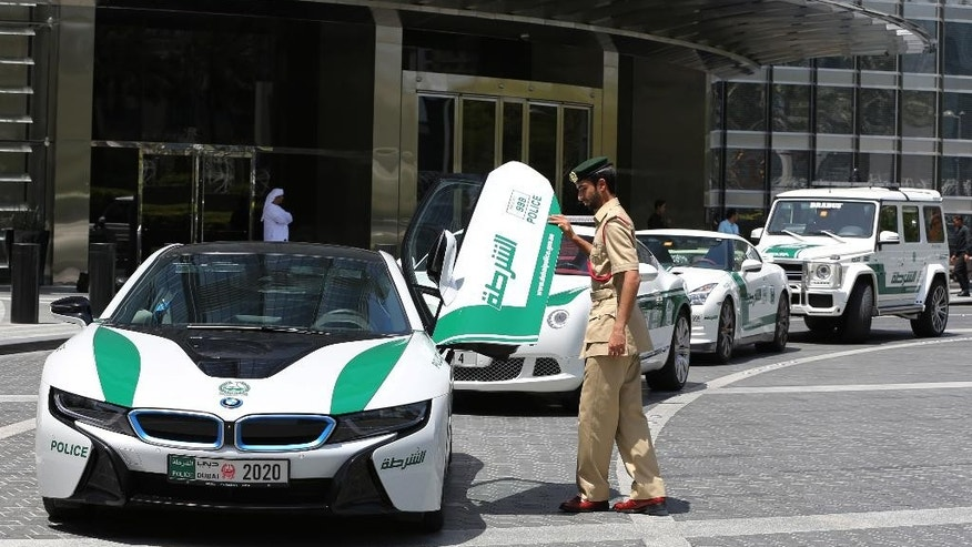In this Thursday May 19, 2016 photo, Dubai police Lt. Saif Sultan Rashed al-Shamsi, who oversees the tourist police's patrol section, pushes down one of the twin scissor doors of the $140,000 BMW i8 during a demonstration in Dubai, United Arab Emirate. Police in Dubai have built up a high-horsepower arsenal of luxury sports cars and SUVs over the years to complement its fleet of green-and-white patrol cruisers. They say it is a way to reach out to the community and make their officers more accessible to the public in a country home to huge foreign workforce. (AP Photo/Kamran Jebreili)