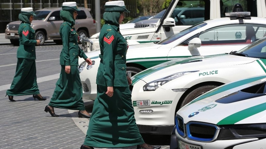In this Thursday May 19, 2016 photo, Dubai police women walk towards their luxury cars during a demonstration in Dubai, United Arab Emirates. Police in Dubai have built up a high-horsepower arsenal of luxury sports cars and SUVs over the years to complement its fleet of green-and-white patrol cruisers. They say it is a way to reach out to the community and make their officers more accessible to the public in a country home to huge foreign workforce. (AP Photo/Kamran Jebreili)