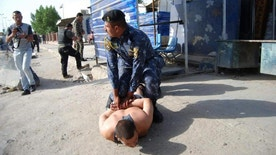 In this image released by Iraq's Federal Police on Wednesday, May 25, 2016, policeman Saad Ali Thabit detains a would-be suicide bomber at a checkpoint north of Baghdad's Kadhimiyah neighborhood. Thabit is being honored as a hero by Iraqi officials and on social media. Closed Circuit video of Thabit discovering and then disarming the would-be bomber during routine searches was quickly shared on social media racking up hundreds of thousands of views Thursday. (Iraq Federal Police via AP)
