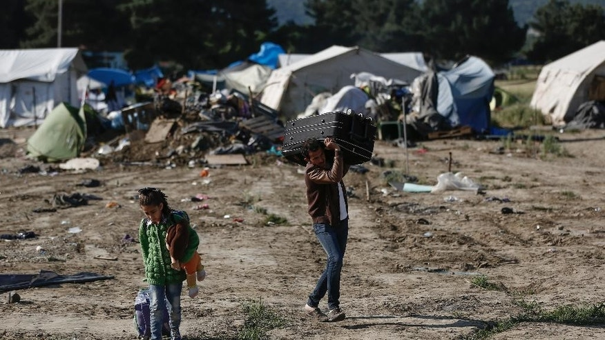 Migrants carry their belongings as they leave a makeshift camp during a police operation at the Greek-Macedonian border near the northern Greek village of Idomeni, Thursday, May 26, 2016. Greek police continue to evacuate the sprawling, makeshift Idomeni refugee camp where more than an estimated 8,400 people have been living for months. (Yannis Kolesidis/ANA-MPA via AP)