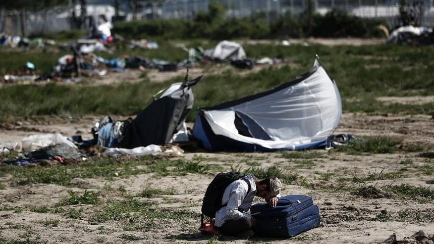 A Kurdish man sits on the ground as he waits to leave a makeshift camp during a police operation at the Greek-Macedonian border near the northern Greek village of Idomeni, Thursday, May 26, 2016. Greek police continue to evacuate the sprawling, makeshift Idomeni refugee camp where more than an estimated 8,400 people have been living for months. (Yannis Kolesidis/ANA-MPA via AP)