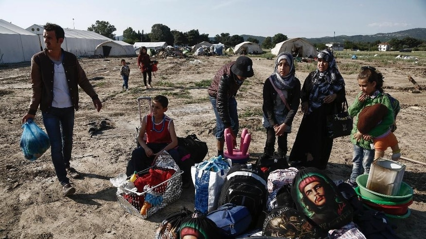 Syrian refugees wait with their belongings to leave from a makeshift camp during a police operation at the Greek-Macedonian border near the northern Greek village of Idomeni, Thursday, May 26, 2016. Greek police continue to evacuate the sprawling, makeshift Idomeni refugee camp where more than an estimated 8,400 people have been living for months. (Yannis Kolesidis/ANA-MPA via AP)