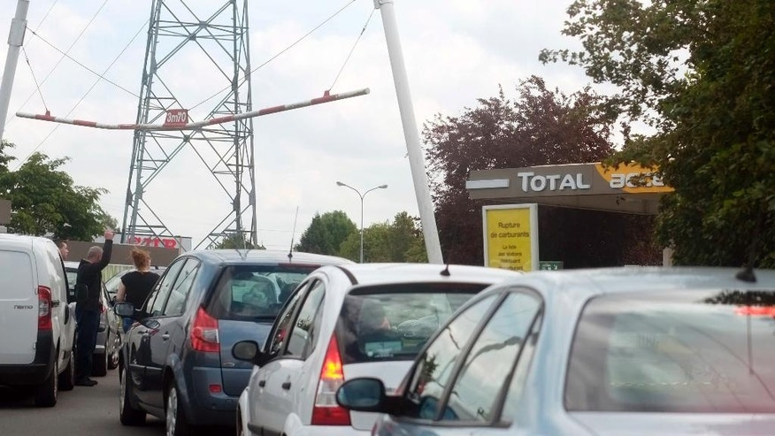 "Cars queue near a poster that reads ""Fuel Shortage"" outside a closed gas station in Villeneuve d'Ascq, near Lille, northern France, Wednesday, May 25, 2016. France has started using its fuel reserves to deal with gasoline shortages caused by strikes and protests over a bill weakening worker protections. (AP Photo/Michel Spingler)"