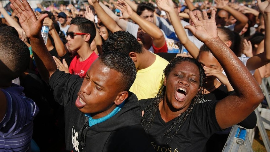 "Christians raise their hands as they sing gospel songs during the annual ""March for Jesus"" in Sao Paulo, Brazil, Thursday, May 26, 2016. Evangelical Christians take part in the annual event that unites faithful from hundreds of Protestant churches in a country that is largely Roman Catholic. The Reborn in Christ Church has organized the march for the past 24 years. (AP Photo/Andre Penner)"