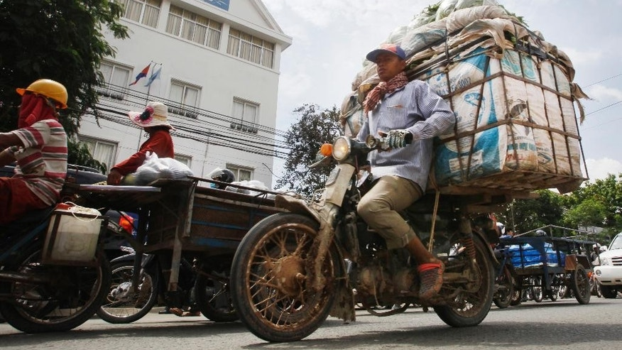 Cambodian motorists ride past the headquarters of the Cambodia National Rescue Party (CNRP), in Phnom Penh, Cambodia, Friday, May 27, 2016. A Cambodian court on Friday convicted three military commandos of beating up two CNRP lawmakers outside the parliament last year, and sentenced them to one year each in prison. The legislators' lawyer called the punishment too lenient. (AP Photo/Heng Sinith)