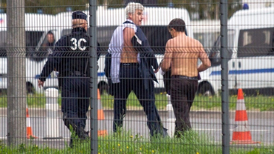 Oct. 5, 2015: Air France director of Human Resources Xavier Broseta, right, and Air France assistant director of long-haul flights Pierre Plissonnier, center, are protected by a police officer as they flee Air France headquarters at Roissy Airport, north of Paris, France, after scuffles with union activists.