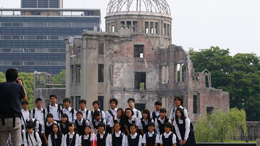 School children pose for a group photo with the Atomic Bomb Dome as a backdrop in Hiroshima Peace Memorial Park in Hiroshima, western Japan, Friday, May 27, 2016. Convinced that the time for this moment is right at last, U.S. President Barack Obama on Friday will become the first American president to confront the historic and haunted ground of Hiroshima. (AP Photo/Shuji Kajiyama)