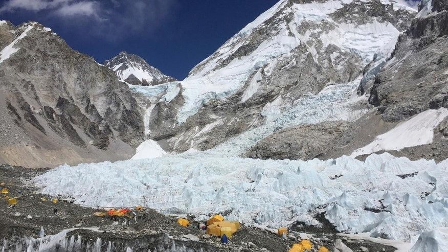 FILE- In this April 10, 2016 photo yellow and orange tents at Everest Base Camp, pitched on the edges of the Khumbu icefall in Nepal. Nearly 300 people have died on Mt. Everest in the century or so since climbers have been trying to reach the summit and at least 100 of them are still on the mountain. (AP Photo/Karin Laub, File)a