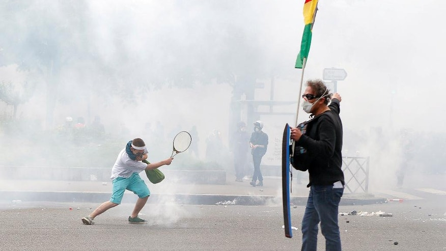 A protestor uses a tennis racket to hit away tear gas fired by police during a demonstration held as part of nationwide labor actions in Paris, France, Thursday, May 26, 2016. French protesters scuffled with police, dock workers set off smoke bombs and union activists disrupted fuel supplies and nuclear plants Thursday in the biggest challenge yet to President Francois Hollande's government as it tries to give employers more flexibility (AP Photo/Francois Mori)
