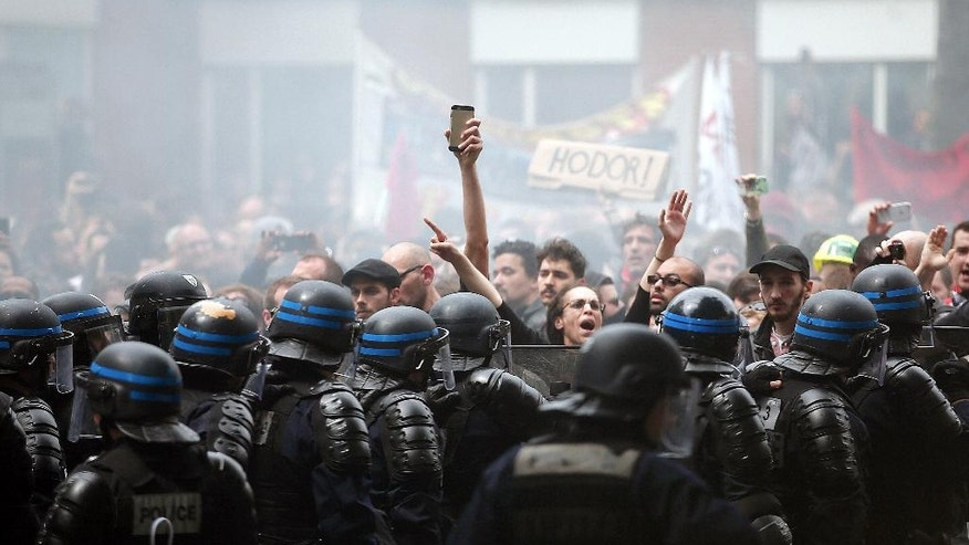 Protestors face riot police officers during a demonstration held as part of nationwide labor actions in Paris, Thursday, May 26, 2016. Paris police have detained nine people and scuffled with masked protesters as several thousand people marched through the French capital to demand that the government scrap a labor bill. (AP Photo/Thibault Camus)