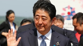 Japanese Prime Minister Shinzo Abe waves to the media after a press conference of the Group of Seven Summit in Shima, central Japan, Friday, May 27, 2016. The G-7 host, Abe appealed to his fellow leaders to act to avert another global crisis, comparing the current global economic situation to conditions just before the 2008 financial crisis. (AP Photo/Shizuo Kambayashi)