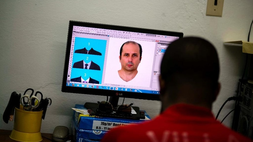 Lian Marrero edits a photo of Miami-based Cuban Javier Fontanella, with digital suit options at left, as he prepares his client's ID photo which he'll use for a Cuban citizenship application in Havana, Cuba, Thursday, May 26, 2016. Across Cuba and the world, tens of thousands of Cubans stare out of ID photos in elegant suits and dressy blouses they have never actually worn. (AP Photo/Ramon Espinosa)