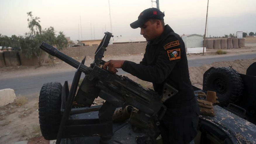 A soldier prepares a heavy weapon at the operations center outside Fallujah, Iraq, on Friday, May 27, 2016, as military forces surround the city.   Iraqi forces launched an offensive on the city of Fallujah, located 65 kilometers (40 miles) west of Baghdad, earlier this week. (AP Photo/Khalid Mohammed)