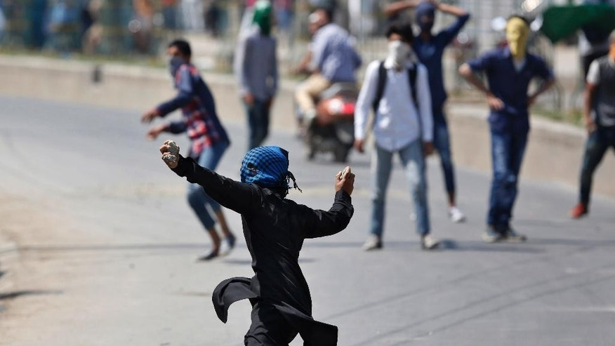 A masked Kashmiri Muslim protester prepares to throw a stone at Indian paramilitary soldiers during a protest in Srinagar, India, Friday, May. 27, 2016. Anti-India separatist leaders called for protest after Friday prayers against alleged plans to construct separate colonies for Indian soldiers and Hindu Kashmiri Pandit community in the valley. (AP Photo/Mukhtar Khan)