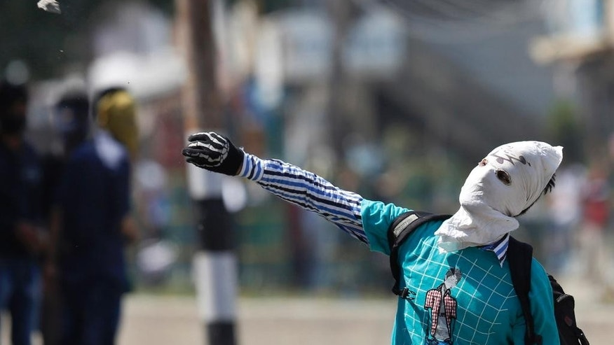 A masked Kashmiri Muslim protester throws a stone at Indian paramilitary soldiers during a protest in Srinagar, India, Friday, May. 27, 2016. Anti-India separatist leaders called for protest after Friday prayers against alleged plans to construct separate colonies for Indian soldiers and Hindu Kashmiri Pandit community in the valley. (AP Photo/Mukhtar Khan)