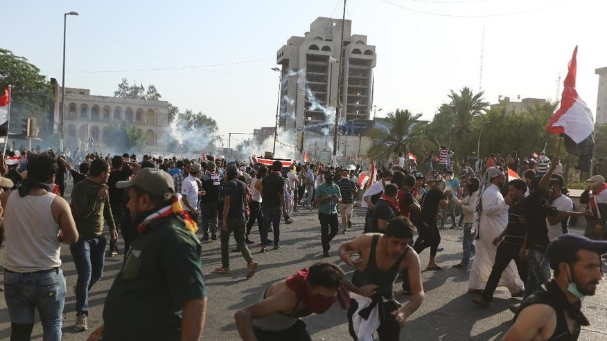 Protesters run from tear gas fired by security forces in central Baghdad, Iraq, Friday, May 26, 2016. Thousands of protesters including followers of influential Shiite cleric Muqtada al-Sadr took to the streets and rallied calling for comprehensive reforms and a new technocrat reshuffle. Dozens of demonstrators suffered from tear gas inhalation.(AP Photo/Hadi Mizban)