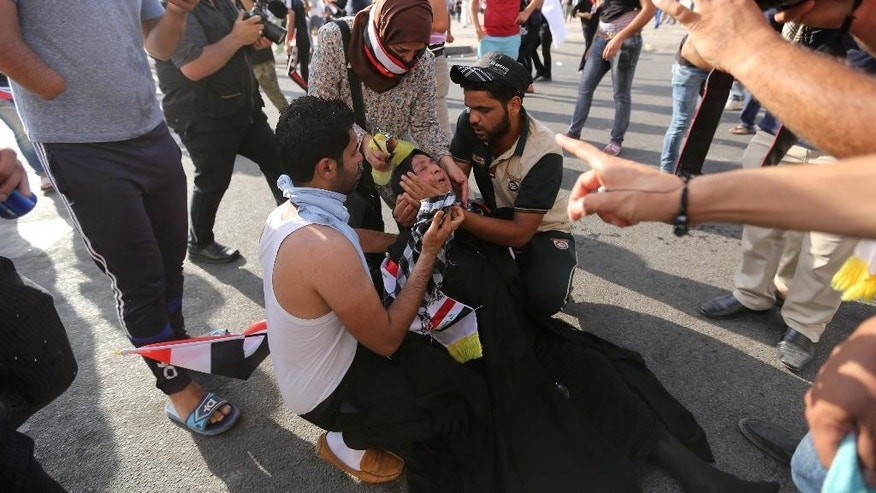 A woman protester is assisted after reacting to tear gas fired by security forces in central Baghdad, Iraq, Friday, May 27, 2016. Thousands of protesters including followers of influential Shiite cleric Muqtada al-Sadr took to the streets and rallied calling for comprehensive reforms and a new technocrat reshuffle. Dozens of demonstrators suffered from tear gas inhalation.(AP Photo/Hadi Mizban)