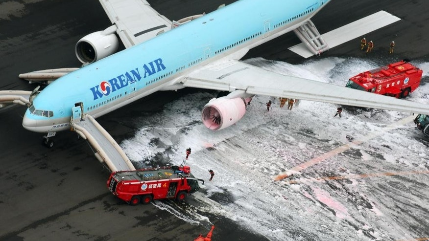 Firefighters gather near an engine of a Korean Air jet following an apparent engine fire on the tarmac at Haneda Airport in Tokyo Friday, May 27, 2016. All the passengers and crew were evacuated unharmed, Japanese media reported. (Kyodo News via AP) JAPA OUT, CREDIT MANDATORY