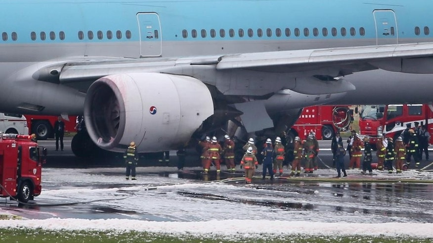 Firefighters work on a Korean Air jet sitting on the white foam-covered tarmac following an engine fire at Haneda Airport in Tokyo Tokyo, Friday, May 27, 2016. The engine fire broke out on the Korean Air jet about to take off from the airport on Friday, and some people may have been injured, an airport official said. Firefighters put out the blaze within the hour, and all passengers and crew were evacuated. (AP Photo/Koji Sasahara)