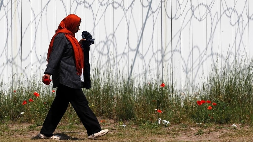 A woman walks by a border fence in the makeshift refugee camp near the Horgos border crossing into Hungary, near Horgos, Serbia, Friday, May 27, 2016. Nearly 400,000 refugees passed through Hungary last year on their way to richer EU destinations. The flow was slowed greatly by Hungary's construction of razor-wire fences on its borders with Serbia and Croatia. (AP Photo/Darko Vojinovic)