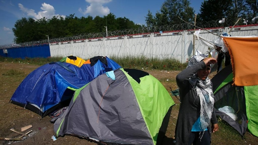 A woman stands in front of her tent in the makeshift refugee camp near the Horgos border crossing into Hungary, near Horgos, Serbia, Friday, May 27, 2016. Nearly 400,000 refugees passed through Hungary last year on their way to richer EU destinations. The flow was slowed greatly by Hungary's construction of razor-wire fences on its borders with Serbia and Croatia. (AP Photo/Darko Vojinovic)