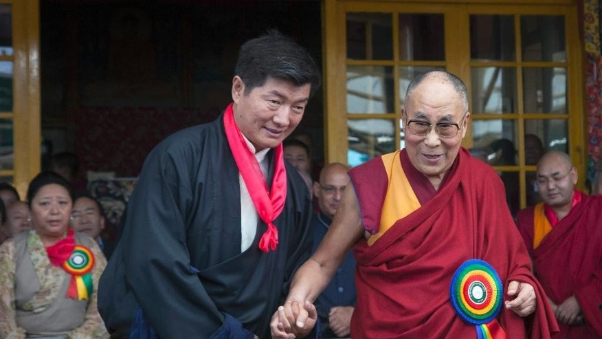 Tibetan spiritual leader the Dalai Lama, right, smiles as he poses for a photograph with Lobsang Sangay, who was sworn in as Prime Minister of the Tibetan government-in-exile for the second five-year term in Dharmsala, India, Friday, May 27, 2016. Sangay was the first elected Tibetan political leader after the Dalai Lama dissolved his powers in 2011. (AP Photo/ Ashwini Bhatia)
