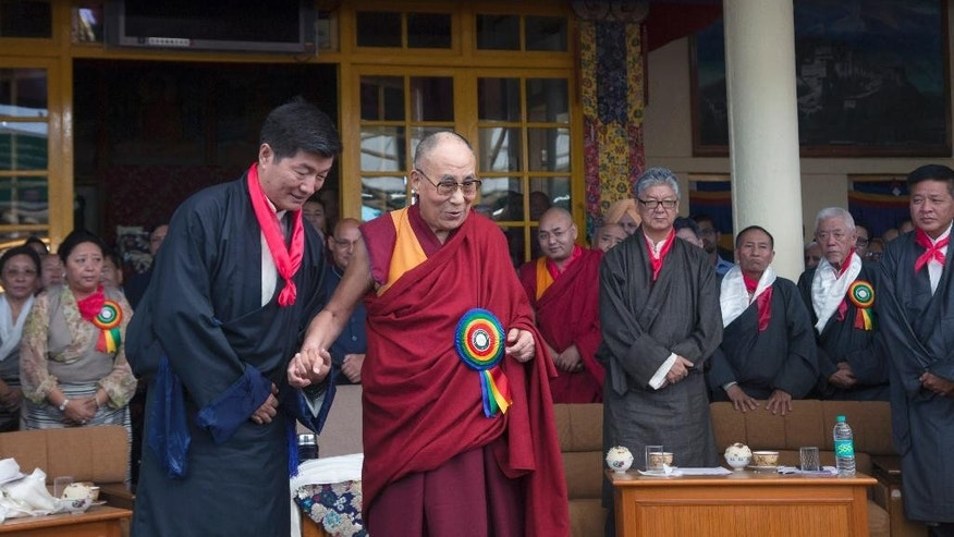 Tibetan spiritual leader the Dalai Lama, center, smiles as he poses for a photograph with Lobsang Sangay, center left, who was sworn in as Prime Minister of the Tibetan government-in-exile for the second five-year term in Dharmsala, India, Friday, May 27, 2016. Sangay was the first elected Tibetan political leader after the Dalai Lama dissolved his powers in 2011. (AP Photo/ Ashwini Bhatia)