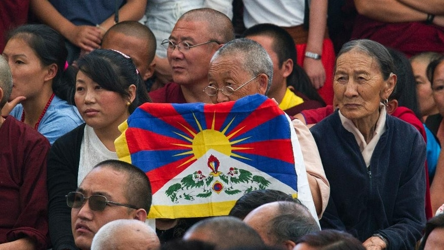 An exiled Tibetan carries a Tibetan flag as she attends the swearing-in ceremony of Lobsang Sangay, who took oath as Prime Minister of the Tibetan government-in-exile for the second five-year term, in Dharmsala, India, Friday, May 27, 2016. Sangay was the first elected Tibetan political leader after the Dalai Lama dissolved his powers in 2011. (AP Photo /Ashwini Bhatia)
