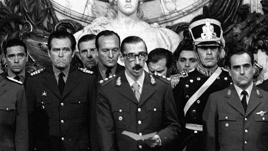 FILE - In this March 24, 1976 file photo, Argentina's dictator Gen. Jorge Rafael Videla, center, is sworn-in as president at the Government House in Buenos Aires, Argentina. With a world divided by the Cold War, South America's dictatorships in 1975 agreed to start exchanging information on political dissidents, trade unionists, students and any individual suspected of being leftist. The goal was to hunt down and eliminate the enemies of the dictatorships across the continent and beyond. According to declassified documents, various agencies of the U.S. government were aware of the plan. (AP Photo/Eduardo Di Baia, File)