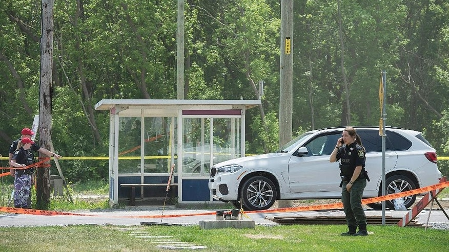 Police officers examine the scene as a white luxury SUV with a broken passenger-side window is shown in Laval, Quebec, Friday, May 27, 2016, where alleged mobster Rocco Sollecito was gunned down earlier this morning. (Graham Hughes/The Canadian Press via AP)