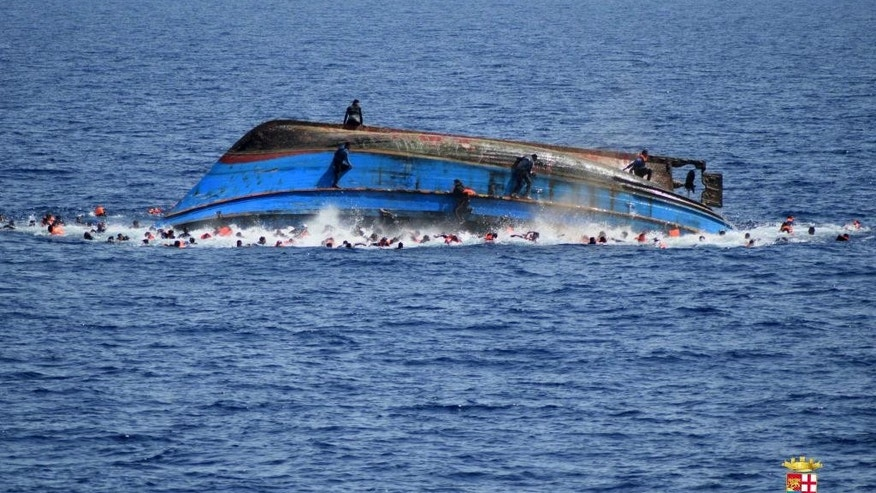 People jump out of a boat right after overturning off the Libyan coast, Wednesday, May 25, 2016. The Italian navy says it has recovered 7 bodies from the overturned migrant ship off the coast of Libya. Another 500 migrants who on board were rescued safely. (Marina Militare via AP Photo)