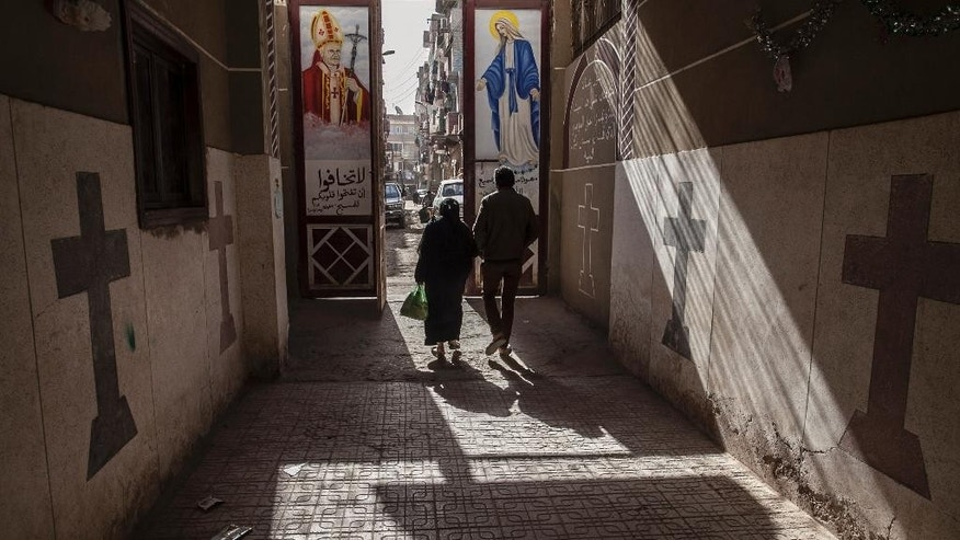 Jan. 6, 2015: Coptic Christians walk outside St. Markos Church in Minya, south of Cairo, Egypt. A Muslim mob ransacked and torched seven Christian homes in a province after rumors spread that a Christian man had an affair with a Muslim woman, according to a statement by the local Orthodox Coptic church.