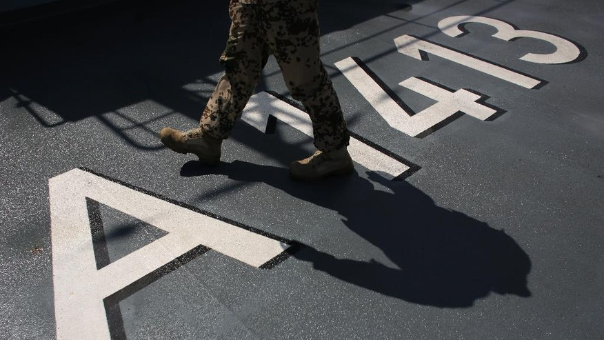 A German soldier walks over the international warship code of the NATO German warship FGS Bonn as the ship departs from the harbor of the city of Izmir, Turkey, Thursday, May 26, 2016. The FGS Bonn is part of the NATO flotilla patrolling the Aegean Sea in an effort to curb migrant activity between Turkey and Greece. (AP Photo/Markus Schreiber)