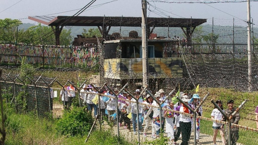 South Korean activists march along the military wire fences during 2016 Women Walk for Korean Peace at the Imjingak Pavilion near the border village of Panmunjom, in Paju, South Korea, Saturday, May 28, 2016. North Korea on Saturday threatened to fire at South Korean warships if they cross a disputed western sea border, a day after the South's navy fired warning shots to chase away two North Korean ships that briefly crossed the boundary.(AP Photo/Ahn Young-joon)