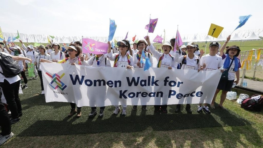 South Korean activists shout during 2016 Women Walk for Korean Peace at the Imjingak Pavilion near the border village of Panmunjom, in Paju, South Korea, Saturday, May 28, 2016. North Korea on Saturday threatened to fire at South Korean warships if they cross a disputed western sea border, a day after the South's navy fired warning shots to chase away two North Korean ships that briefly crossed the boundary.(AP Photo/Ahn Young-joon)