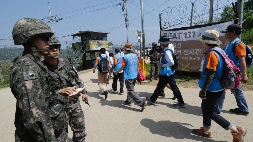 South Korean activists march along the military wire fences as South Korean army soldiers stand guard during 2016 Women Walk for Korean Peace at the Imjingak Pavilion near the border village of Panmunjom, in Paju, South Korea, Saturday, May 28, 2016. North Korea on Saturday threatened to fire at South Korean warships if they cross a disputed western sea border, a day after the South's navy fired warning shots to chase away two North Korean ships that briefly crossed the boundary.(AP Photo/Ahn Young-joon)