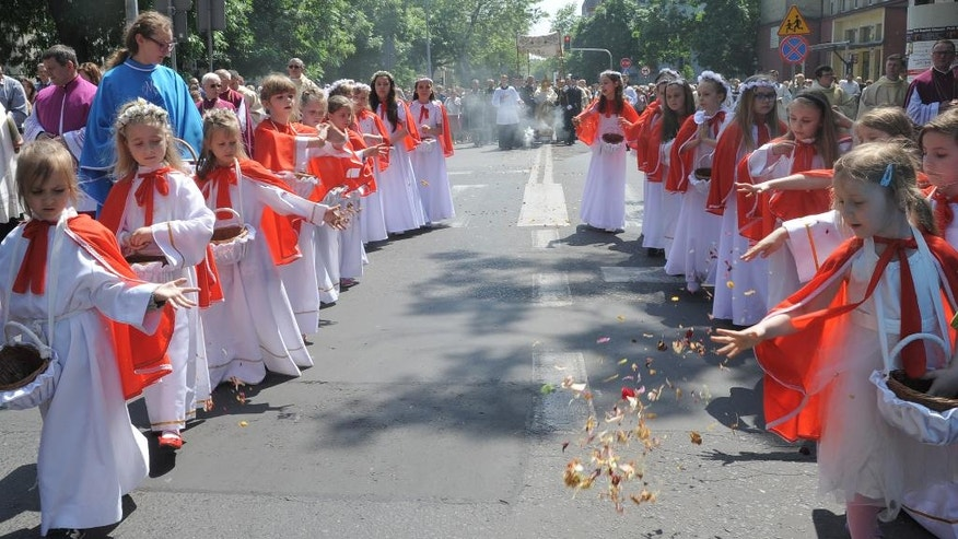 Girls throw flower petals during a procession celebrating the Catholic Feast of Corpus Christi, in Warsaw, Poland, Thursday, May 26, 2016. (AP Photo/Alik Keplicz)